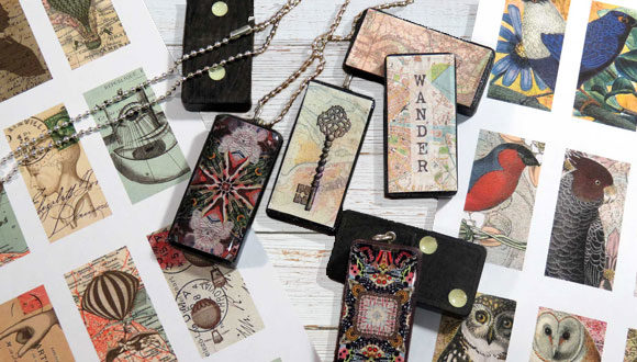 photograph of table top with domino pendant necklaces and vintage images