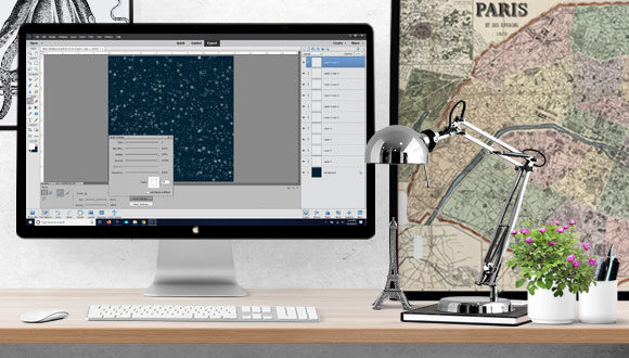 photograph of desk with computer screen with Photoshop Elements software open and lamp and poster
